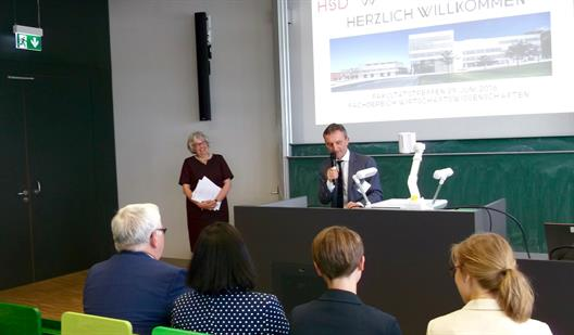 One sees the dean of the Faculty of Economics, Prof. Dr. Albers and Thomas Geisel, Mayor of Dusseldorf. They stand at the head of a lecture hall. Mr. Geisel stands at the lectern and is talking into a microphone. Prof. Dr. Albers ist standing on the left.