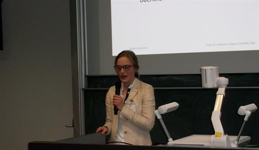 One sees Mrs. Céline Fabienne Lücken, a graduate of the BKM program and winner of GDD Science Prize, speaking into a microphone.