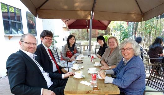 "We see six people who sit outside under an umbrella at a long table. From left to right: Prof. Dr. Peter C. Fischer, Prof. Dr. Lothar Funk, Professor Dr. Lei Zhang, Ms. Heilun Zhu, General Manager ""Visit Beijing Top World Color Plating and Printing Company"", a former student of Prof. Zhang, President Prof. Dr. Brigitte Grass, Dean Prof. Dr. Felicitas Albers"