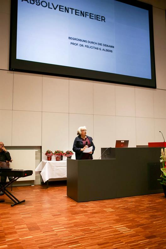 A lady with grizzled hair (Dean Felicitas G. Albers) stands at the lectern of the main lecture hall and talks to the guests.