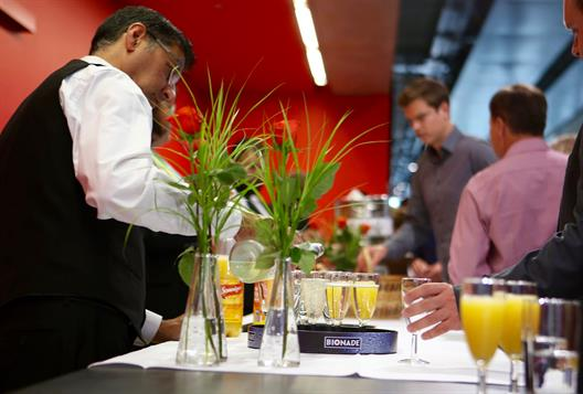 One sees a flowery counter. Waiters serve champagne, orange juice and soft drinks.