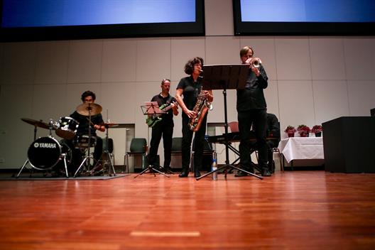 The band consists of a drummer, an electric bassist, a saxophonist. a trumpet player and a keyboard player.