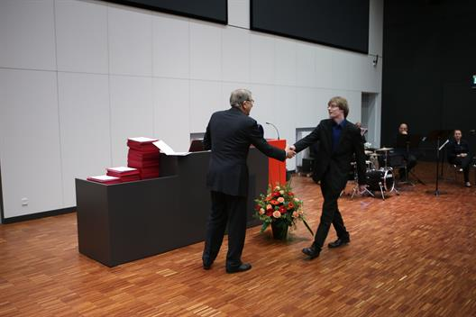 We see an elderly gentleman and a young man, who give themselves hand in front of a lectern.