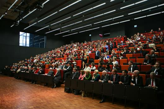 We see the main auditorium of the University of Applied Sciences Dusseldorf. On the ascending rows of seats are sitting many festively dressed people of different ages. There are mostly graduates with their parents and professors.