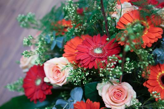 We see a bouquet with flowers in different reds, oranges and rose tones.