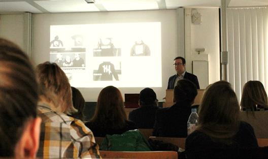 One sees a man with glasses, wearing a dark jacket. He stands at the head of a lecture hall. His presentation shows pictures from a fashion blog.