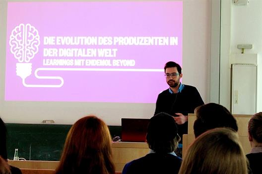 "We see a young man with a beard, dark hair and glasses. He is standing behind a lectern and shows a presentation, that is entitled ""The Evolution of the producer in the digital world""."