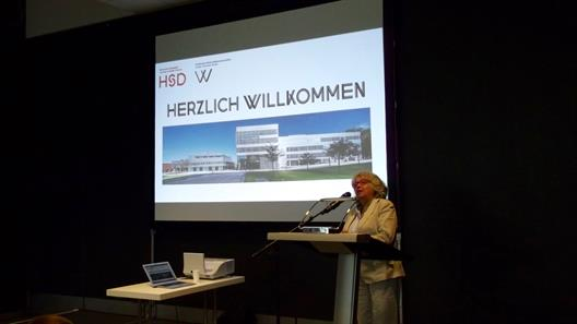"The Dean Prof. Dr. Felicitas Albers stands at the head end of a hall on a lectern. In the background, a presentation is being projected onto a background. The current chart shows the logo of the university and the faculty, the word ""Welcome"" and an exterior view of the building in which the department is located."