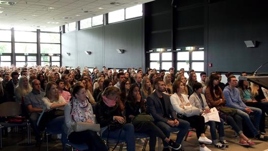 Approximately 300 freshmen are seated in a large hall and follow the presentations of the department and the friends´ association.