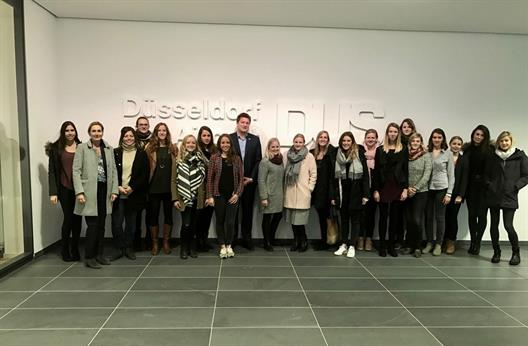 "The picture shows a group of 19 young women grouped in front of a wall. In the background is a very large plastic white logo with the inscription ""Düsseldorf Airport DUS"". Also on the picture are Prof. Dr. Kalka and Mr. Thomas Kötter."