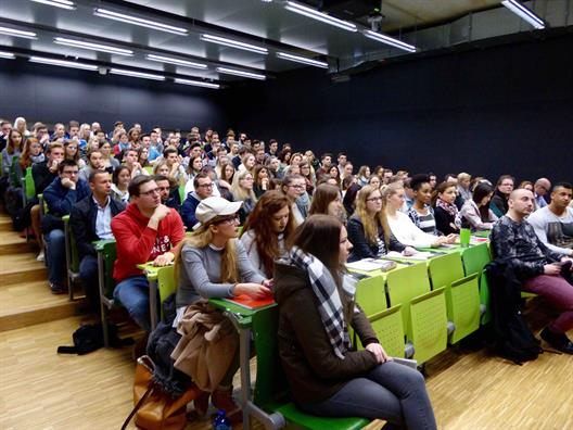 We see many young people who are sitting in an auditorium with rising rows of seats. The auditorium is obviously new. Characteristic features are the green chairs and the bright parquet.