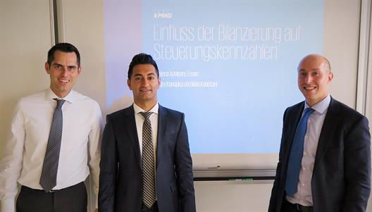 "One sees Mr Andre Konopka (right), Mr. Masi Kohistani (middle ) and Prof. Dr. Jödicke (left). They stand at the head of a lecture room. Behind them you can see the title of their presentation. It is ""Impact of accounting on control measures."""