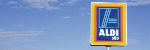 "One sees a sign for the market discount chain ALDI Süd against a blue sky. The sign consists of a stylized blue ""A"" and the white signature ""ALDI SÜD"". The inner logo is framed of the colors red , orange and yellow."