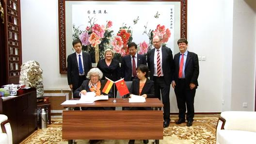 One sees a desk that is decorated with the German and the Chinese flag. Two ladies who want to sign the cooperation agreement sit at it. Behind them are German and Chinese delegation members .