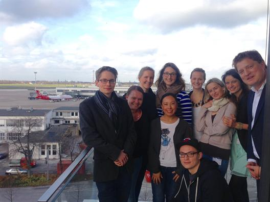 One sees nine female students and one male student standing on a balcony. On their right is the Head of Corporate Communications Düsseldorf Airport, Mr. Thomas Kötter . In the background is a passenger plane, parts of the runway and a terminal building.