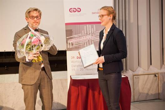 One sees a stage on which a man in a suit with glasses, blonde hair and beard is preparing to hand over a bouquet of flowers. To his right is the winner, she holds a diploma in hand. She is a young woman with blond hair and glasses, dressed in jeans, white blouse and black blazer.