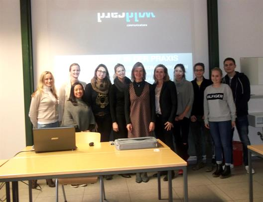 One sees Mrs. Ira Reckenthäler, CMO of wildcard communications GmbH  together with the students of the major subjects Corporate and Market Communication. They stand side by side at the head of a lecture room. In the background, a projector throws the lecture titles and the logo of wildcard communications on the wall.