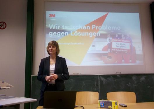 "We see a lady standing at the head of a lecture room. In the background, the start screen of a presentation is shown. It shows the slogan ""We exchange problems to solutions"" and four people sitting on a large three-dimensional 3M logo ."