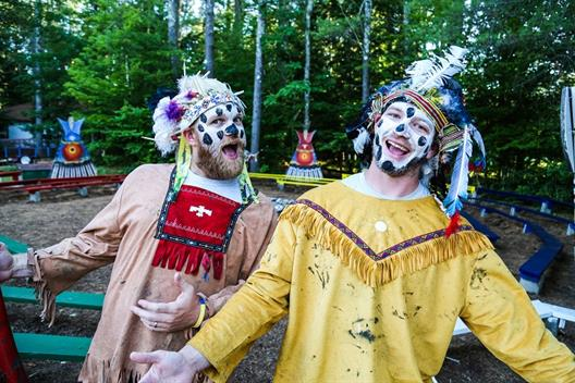 "One sees two young men, which are disguised as Indians, spreading agood mood. In the background is the site of ""Camp America"", a summer camp for children."