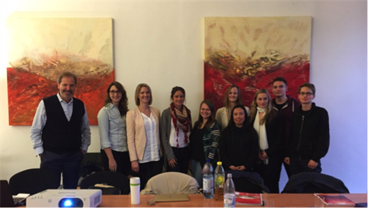 We see a group of students who are in a conference room standing behind a desk. On the wall behind them you see two modern abstract paintings, which are mainly held in reds and browns. To the left is Mr. Kai vom Hoff.